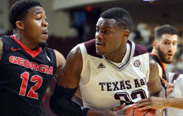 Texas A&M guard Danuel House (23) drives the lane against Georgia's Kenny Gaines (12) during the first half of a NCAA college basketball game at Reed Arena in College Station, Texas on Wednesday, Feb. 11, 2015. (AP Photo/College Station Eagle, Sam Craft)