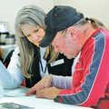 Art Hughes (right) and his wife, Cathy Hughes, review an election report Tuesday produced by Craig S...