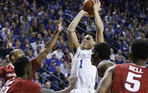 Kentucky's Devin Booker (1) shoots amid Arkansas defenders during the first half of an NCAA college basketball game, Saturday, Feb. 28, 2015, in Lexington, Ky. (AP Photo/James Crisp)