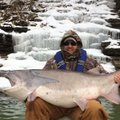 With a frozen waterfall behind him, Jessie Wilkes of Springdale shows the 105-pound paddlefish he ca...