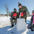 Micah Hulvey (from left), 15, Mitchell Hulvey, 13, and Mikayla Hulvey, 11, build a snow fort Thursda...