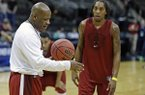 Arkansas head coach Mike Anderson, left, talks with players, including guard Michael Qualls, right, during practice for an NCAA college basketball second-round game Wednesday, March 18, 2015, in Jacksonville, Fla. Arkansas is to play Wofford on Thursday. (AP Photo/John Raoux)