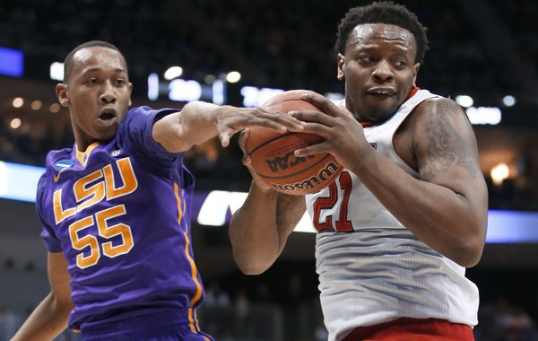 North Carolina State's Beejay Anya (21) holds the ball as LSU's Tim Quarterman (55) tries to get it during the first half of an NCAA tournament second round college basketball game, Thursday, March 19, 2015, in Pittsburgh. (AP Photo/Gene J. Puskar)