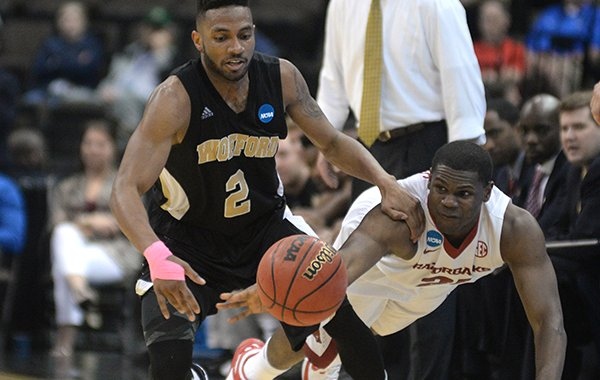 Wofford guard Karl Cochran (2) and Arkansas guard Manuale Watkins go for a loose ball during the second half of an NCAA tournament second round college basketball game Thursday, March 19, 2015, in Jacksonville, Fla. (AP Photo/Rick Wilson)