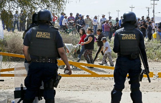 mexican-state-police-keep-an-eye-on-some-of-the-thousands-of-striking-farmworkers-in-san-quentin-baja-california-mexico-on-march-19-2015-in-recent-days-hundreds-of-striking-strawberry-pickers-have-abandoned-the-harvest-burned-tires-blocked-produce-trucks-and-all-but-shut-down-the-lucrative-winter-export-strawberry-harvest-don-bartlettilos-angeles-timestns