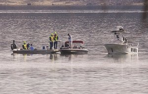 File Photo/J.T. WAMPLER Members of the Rocky Branch Fire Department, the Benton County Sheriffs Office and the Mennonite Disaster Service search Beaver Lake on Wednesday for a missing woman who fell overboard Tuesday.
