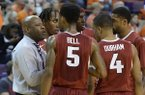 Arkansas head coach Mike Anderson, left, talks to his players during the second half of an NCAA college basketball game against Clemson, Sunday, Dec. 7, 2014, in Clemson, S.C. Clemson won 68-65. (AP Photo/Richard Shiro)