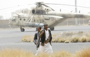 Shiite Houthi rebels stand guard Saturday on the tarmac at Sanaa International Airport in Yemen. Commercial flights to the country have been cut off.