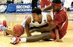 NWA Democrat-Gazette/Michael Woods RUMINATING RAZORBACKS: Arkansas forward Bobby Portis and North Carolina guard Nate Britt get tangled up going after a loose ball during the first half of an NCAA third-round game March 21 at Veterans Memorial Arena in Jacksonville, Fla. Southeastern Conference player of the year Portis and teammate Michael Qualls continue to weigh their NBA options after standout underclassman campaigns.
