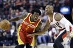 Houston Rockets guard Patrick Beverley, left, drives on Portland Trail Blazers guard Damian Lillard during the first half of an NBA basketball game in Portland, Ore., Wednesday, March 11, 2015. (AP Photo/Don Ryan)