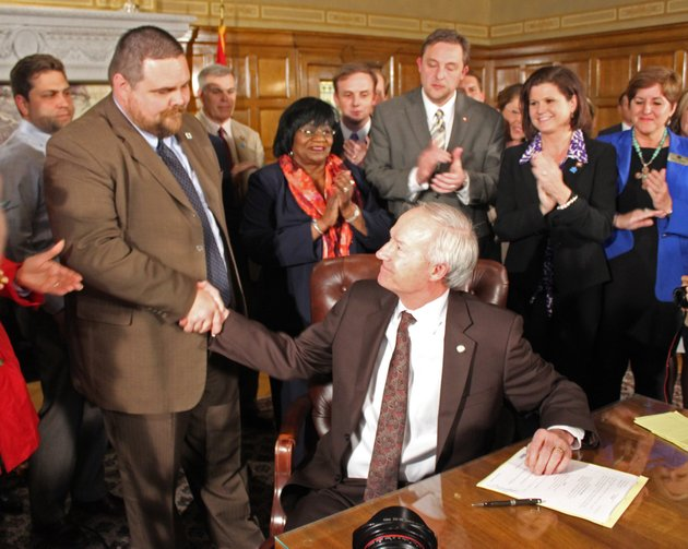gov-asa-hutchinson-shakes-hands-with-rep-bob-ballinger-after-he-signed-senate-bill-975-into-law-on-thursday