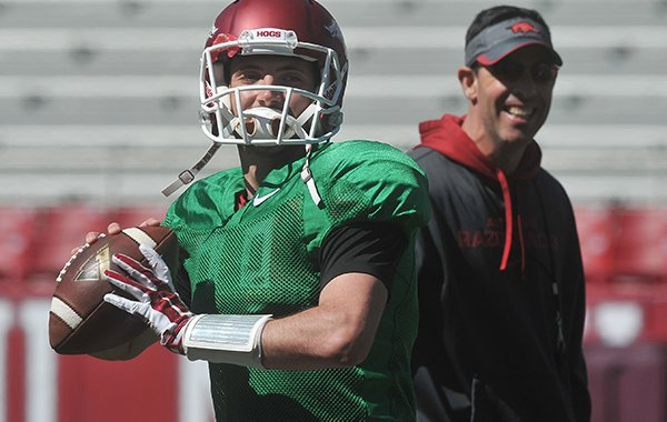 Arkansas quarterback Brandon Allen throws a pass while offensive coordinator Dan Enos watches during practice Saturday, April 4, 2015, at Razorback Stadium in Fayetteville.