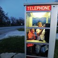 Mason McCourt, 13, (left) and Blake Williams, 14, call friends Thursday from the pay telephone booth...