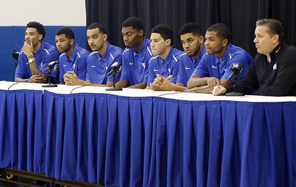 From left, Kentucky NCAA college basketball players Willie Cauley-Stein, Andrew Harrison, Trey Lyles, Dakari Johnson, Devon Booker, Karl-Anthony Towns and Aaron Harrison announce their intent to place their names in the NBA draft during a news conference accompanied by head coach John Calipari, right, at the Joe Craft Center, Thursday, April 9, 2015, in Lexington, Ky. (AP Photo/James Crisp)