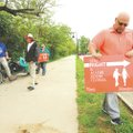 Daniel Butterfield (right), places a sign along Scull Creek Trail on Wednesday while working with Da...