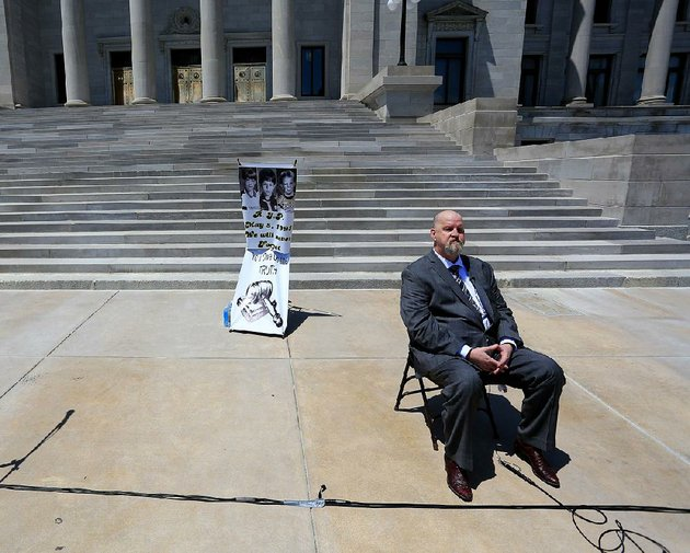 john-mark-byers-adoptive-father-of-christopher-byers-sits-at-the-state-capitol-on-tuesday-during-an-event-calling-for-justice-in-the-slayings-of-8-year-olds-christopher-stevie-branch-and-michael-moore-photos-on-poster-left-in-west-memphis-in-1993