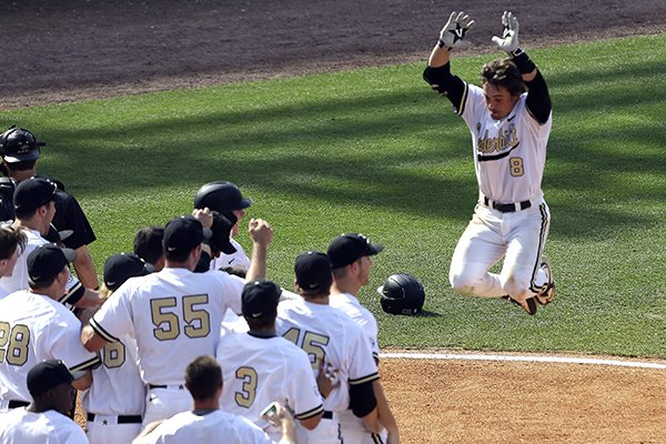 Vanderbilt's Rhett Wiseman (8) jumps into the air celebrating as he approaches home plate after he hit a walk off home run during the 10th inning of a game to defeat Missouri 7-6 at the Southeastern Conference college baseball tournament at the Hoover Met, Wednesday, May 20, 2015, in Hoover, Ala. (AP Photo/Butch Dill)