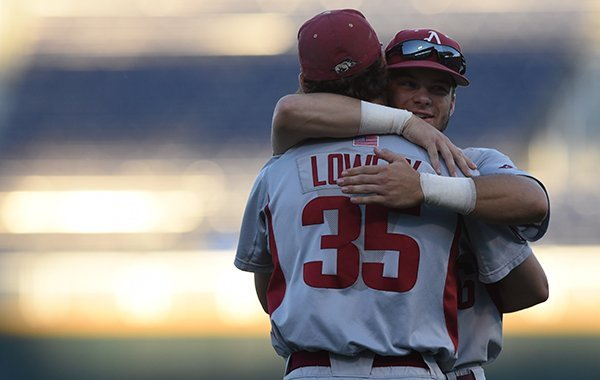 Arkansas outfielder Andrew Benintendi hugs pitcher Jackson Lowery (35) following a game Monday, June 15, 2015, at TD Ameritrade Park in Omaha, Neb.