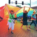 Participants walk Saturday while carrying a large rainbow flag during the NWA Pride Parade on Dickso...