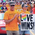 Participants walk Saturday while carrying flags and posters during the NWA Pride Parade on Dickson S...