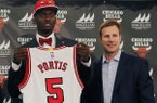 Chicago Bulls Head Coach, Fred Hoilberg, right, stands with the Chicago Bulls first round draft pick, Bobby Portis, from the University of Arkansas, as Portis holds his Bulls jersey after being introduced as the Bulls' top pick during an NBA basketball news conference Monday, June 29, 2015, in Chicago. (AP Photo/Christian K. Lee)