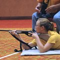 Emma Tichy, a competitor from North Dakota, practices her marksmanship Friday with her coach, Dan Ge...