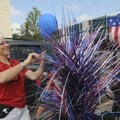 Carolyn Mitchell decorates a golf cart that was part of the Fourth of July Patriot Parade Saturday a...