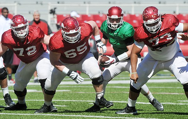 Arkansas offensive linemen Frank Ragnow (72), Mitch Smothers (65) and Sebastian Tretola (73) block while quarterback Brandon Allen runs a play during practice Saturday, April 4, 2015, at Razorback Stadium in Fayetteville.