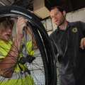 Blake Harrison (left) shows how to repair a flat tire July 16 with help from bike-repair instructor ...