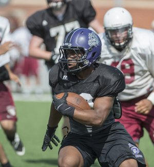 Javentae Smith of Fayetteville sprints up field Monday at a summer team football camp at Jarrell Williams Bulldog Stadium in Springdale.