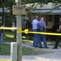Springdale police officers wait Friday outside a home on the corner of Gibbs Road and Nichols Road i...