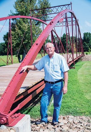 Jerry Pendergraft, Danville city manager, stands next to the Danville-Mickles Bridge, the second oldest bridge in Arkansas. The city of Danville and Yell County led a restoration effort for the bridge, which once was located over the Petit Jean River. The bridge was moved from its original location and restored, and now sits as part of a walking trail next to the Danville City Hall.