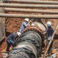A Fayetteville Water and Sewer Department crew repair a 42-inch water line Friday in a field south o...