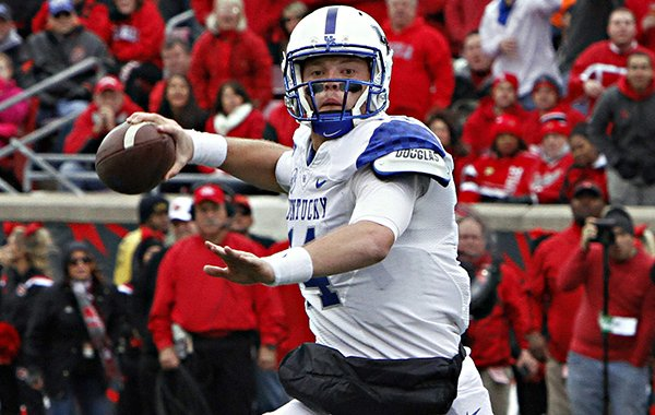 In this Nov. 29, 2014, file photo, Kentucky quarterback Patrick Towles looks to pass against rival Louisville in their NCAA college football game in Louisville, Ky. Coach Mark Stoops has named junior incumbent Patrick Towles as his starting quarterback ahead of Drew Barker. (AP Photo/Garry Jones, File)