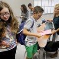 Kenton Lambert (center), a freshman at Fayetteville High School, reviews his class schedule with his...
