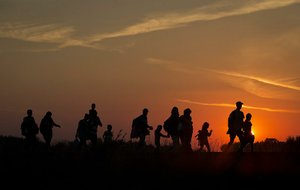 Migrants are silhouetted against the setting sun Sunday as they walk on railway tracks in Roszke, Hungary. On Sunday, Hungary completed a razor-wire fence to keep migrants from entering through its border with Serbia.
