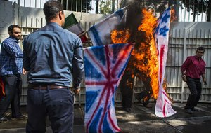 Iranian students burn effigies of British, U.S. and Israeli flags Wednesday at an unveiling of an anti-U.S. plaque at the gate of the former U.S. Embassy in Tehran. The plaque includes a list of condemnations of America uttered by the Islamic republic's late founder, Grand Ayatollah Ruhollah Khomeini.