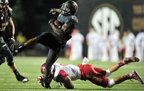 Vanderbilt running back Ralph Webb (7) gets away from a tackle attempt by Western Kentucky defensive back Branden Leston (31) during the second quarter of an NCAA college football game in Nashville, Tenn., Thursday, Sept. 3, 2015. (Jae S. Lee / The Tennessean via AP)