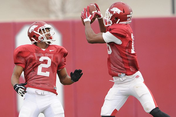 Arkansas cornerbacks D.J. Dean (2) and Cornelius Floyd work through drills during practice Saturday, Dec. 13, 2014, at the university's practice facility in Fayetteville.