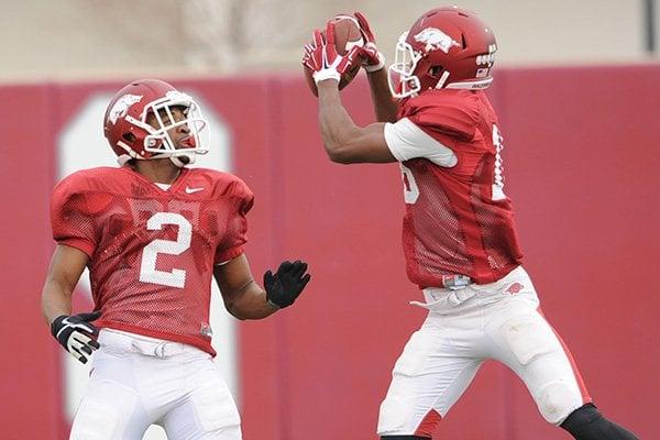 Arkansas cornerbacks D.J. Dean (2) and Cornelius Floyd work through drills during practice Saturday, Dec. 13, 2014, at the university's practice facility in Fayetteville.