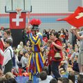St. Vincent de Paul Catholic School students dressed in Swiss attire and carrying Swiss flags march ...
