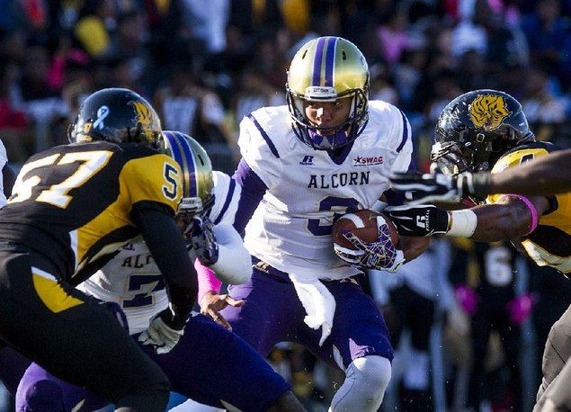 Alcorn State quarterback John Gibbs Jr. pushes through the UAPB defense during Saturday's game at War Memorial Stadium in Little Rock. Gibbs ran for 3 touchdowns and passed for 2 as the Braves beat the Golden Lions 61-14. (Photo by Melissa Gerrits)