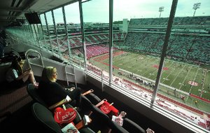 Hannah Story (left) and Cheryl Story of Fayetteville watch pre-game activities from the Arvest Bank suite in Donald W. Reynolds Razorback Stadium as the University of Arkansas prepares to play Texas Tech on Sept. 19.