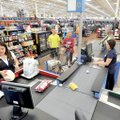Wal-Mart shoppers Cameron and Amy Scott are checked out Wednesday by Wal-Mart employees Daniele Gonz...