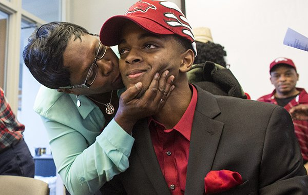 Janice Birt kisses her nephew, Daryl Macon, after he signed with the Arkansas Razorbacks' basketball team on Thursday, Nov. 12, 2015 at the Little Rock Chamber of Commerce.