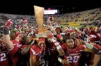 Arkansas players celebrate with the boot after defeating LSU on Saturday, Nov. 14, 2015, in Baton Rouge, La.