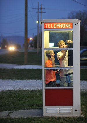 Prairie Grove teenagers Mason McCourt (left) and Blake Williams use the telephone booth on U.S. 62 in Prairie Grove in April, when the booth was first nominated to the National Register of Historic Places.