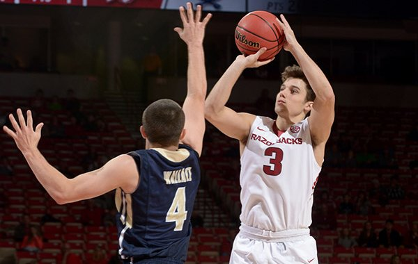 Dusty Hannahs of Arkansas sinks a 3-point basket over Patrick Wallace of Charleston Southern on Friday, Nov. 20, 2015, during a game in Bud Walton Arena in Fayetteville.