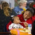 Dalia Flores feeds her daughter, Jennifer Flores, 10 months, both of Springdale, on Tuesday during t...