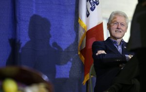 In this Nov. 15, 2015 file photo, former President Bill Clinton listens to his wife, Democratic presidential candidate Hillary Rodham Clinton speak in Ames, Iowa.